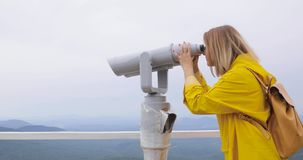 Donna in impermeabile giallo che esamina tramite il binocolo turistico le montagne video d archivio