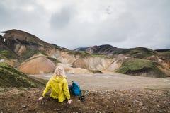 Donna in impermeabile giallo che trascura le montagne colourful nel parco nazionale di Landmannalaugar, Islanda immagine stock