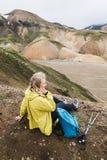 Donna in impermeabile giallo che trascura le montagne colourful nel parco nazionale di Landmannalaugar, Islanda immagini stock
