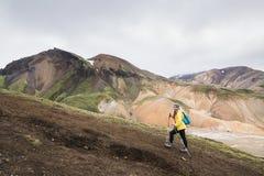 Donna in impermeabile giallo che trascura le montagne colourful nel parco nazionale di Landmannalaugar, Islanda fotografie stock libere da diritti