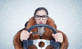 Donna importante in vetri e una pelliccia che conduce un'automobile nella neve Su priorità bassa blu immagine stock