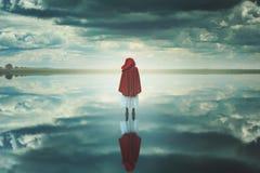 Donna incappucciata rossa in un paesaggio sconosciuto con le nuvole Immagini Stock