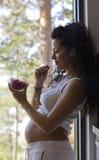 Donna incinta accanto alla finestra Fotografia Stock