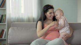 Donna incinta allegra che abbraccia piccola neonata sveglia, amore e tenerezza archivi video