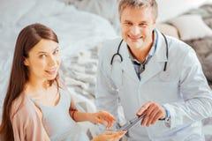 Donna incinta allegra e medico che sorridono nella macchina fotografica Fotografia Stock