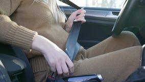 Donna incinta in automobile, in pancia di segno femminile in grande aspettativa preoccupantesi e nella deformazione sulla cintura video d archivio
