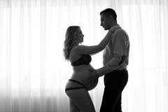 Donna incinta in bianco e nero ed il suo marito Immagini Stock