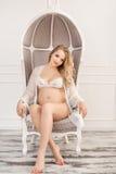 Donna incinta bionda in biancheria intima bianca dell'interno sulla sedia Fotografia Stock Libera da Diritti