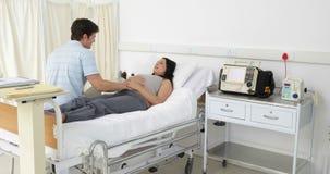 Donna incinta castana che si trova sul letto che parla con il partner video d archivio