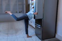 Donna incinta che cerca alimento in frigorifero fotografie stock