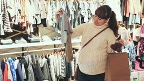 Donna incinta che cerca i vestiti per il bambino nel negozio di vestiti del ` s dei bambini archivi video