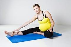 Donna incinta che effettua stirata del piedino Immagine Stock Libera da Diritti