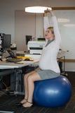 Donna incinta che esegue allungando esercizio sulla palla di forma fisica Fotografia Stock Libera da Diritti