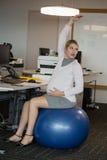 Donna incinta che esegue allungando esercizio sulla palla di forma fisica Immagine Stock Libera da Diritti