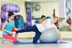 Donna incinta che fa esercizio della palla di forma fisica con la vettura Fotografia Stock