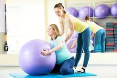 Donna incinta che fa esercizio della palla di forma fisica con la vettura Fotografie Stock