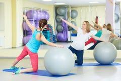 Donna incinta che fa esercizio della palla di forma fisica con la vettura Immagini Stock
