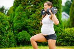 Donna incinta che fa gli affondo di inginocchiamento con le teste di legno in parco fotografia stock