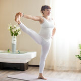 Donna incinta che fa mano estesa alla posa di yoga dell'alluce a casa Fotografia Stock Libera da Diritti