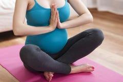 Donna incinta che fa yoga Immagine Stock