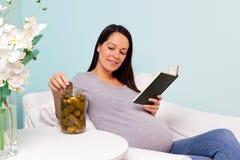 Donna incinta che ha bisogno per il cetriolino marinato. fotografia stock