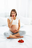 Donna incinta che mangia fragola a casa Concetto sano dell'alimento immagine stock libera da diritti