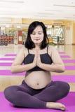 Donna incinta che medita nel centro di forma fisica Fotografia Stock
