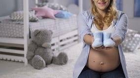 Donna incinta che mostra i bottini del bambino alla macchina fotografica archivi video