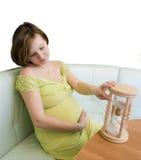 Donna incinta che osserva sulla clessidra Fotografia Stock
