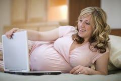 Donna incinta che per mezzo del computer portatile Fotografia Stock