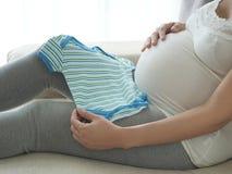 Donna incinta che prepara i vestiti del bambino Immagini Stock Libere da Diritti