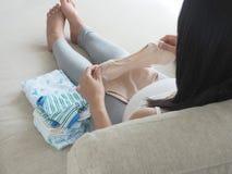 Donna incinta che prepara i vestiti del bambino Fotografia Stock