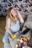 Donna incinta che riposa sul sofà e che parla sul telefono Immagini Stock