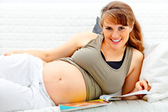 Donna incinta che si distende sul sofà con lo scomparto Fotografia Stock Libera da Diritti