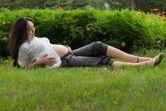 Donna incinta che si distende sull'erba fotografie stock libere da diritti