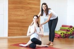 Donna incinta che si esercita, aiuto dell'istruttore Yoga di gravidanza immagini stock libere da diritti
