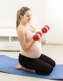 Donna incinta che si esercita con le teste di legno sulla stuoia di forma fisica Fotografia Stock