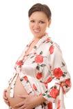 Donna incinta che si leva in piedi su una priorità bassa bianca Immagine Stock
