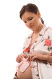 Donna incinta che si leva in piedi su una priorità bassa bianca Fotografie Stock