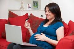 Donna incinta che si siede sul negozio di Sofa Using Credit Card To online Immagini Stock Libere da Diritti