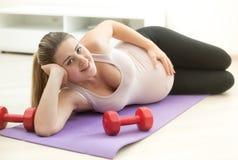 Donna incinta che si trova sulla stuoia di forma fisica con le teste di legno al roo vivente Fotografia Stock