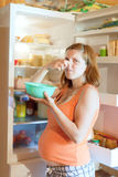 Donna incinta che tiene alimento ripugnante Fotografia Stock Libera da Diritti