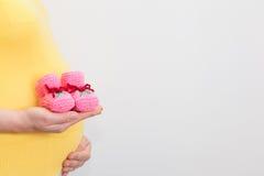 Donna incinta che tiene le scarpe di bambino rosa sulla sua pancia fotografia stock