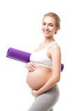 Donna incinta che tiene una stuoia porpora di esercizio Immagine Stock