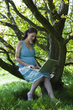 Donna incinta che utilizza computer portatile nel legno Immagine Stock Libera da Diritti