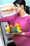 Donna incinta con alimento immagini stock