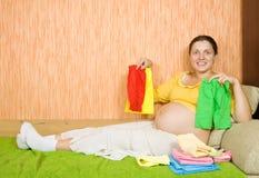 Donna incinta con i vestiti del bambino Fotografia Stock