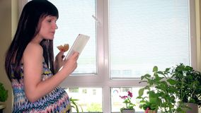 Donna incinta con il computer della compressa che mangia dolce sul fondo della finestra archivi video