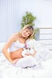 Donna incinta con il giocattolo della peluche fotografia stock libera da diritti