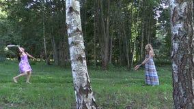 Donna incinta con il gioco di volano del gioco della ragazza della figlia in parco Immagine Stock